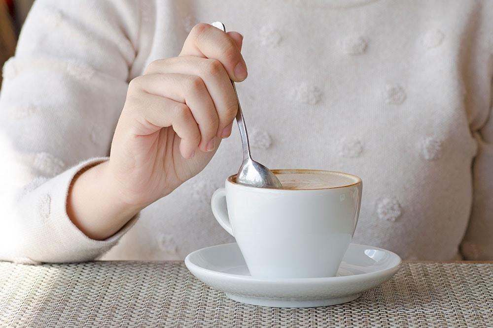 Ženská ruka se lžičkou a šálkem kávy na schůzce