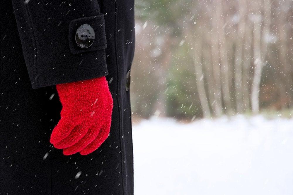 Žena s červenými rukavicemi v zimní krajině s padajícím sněhem